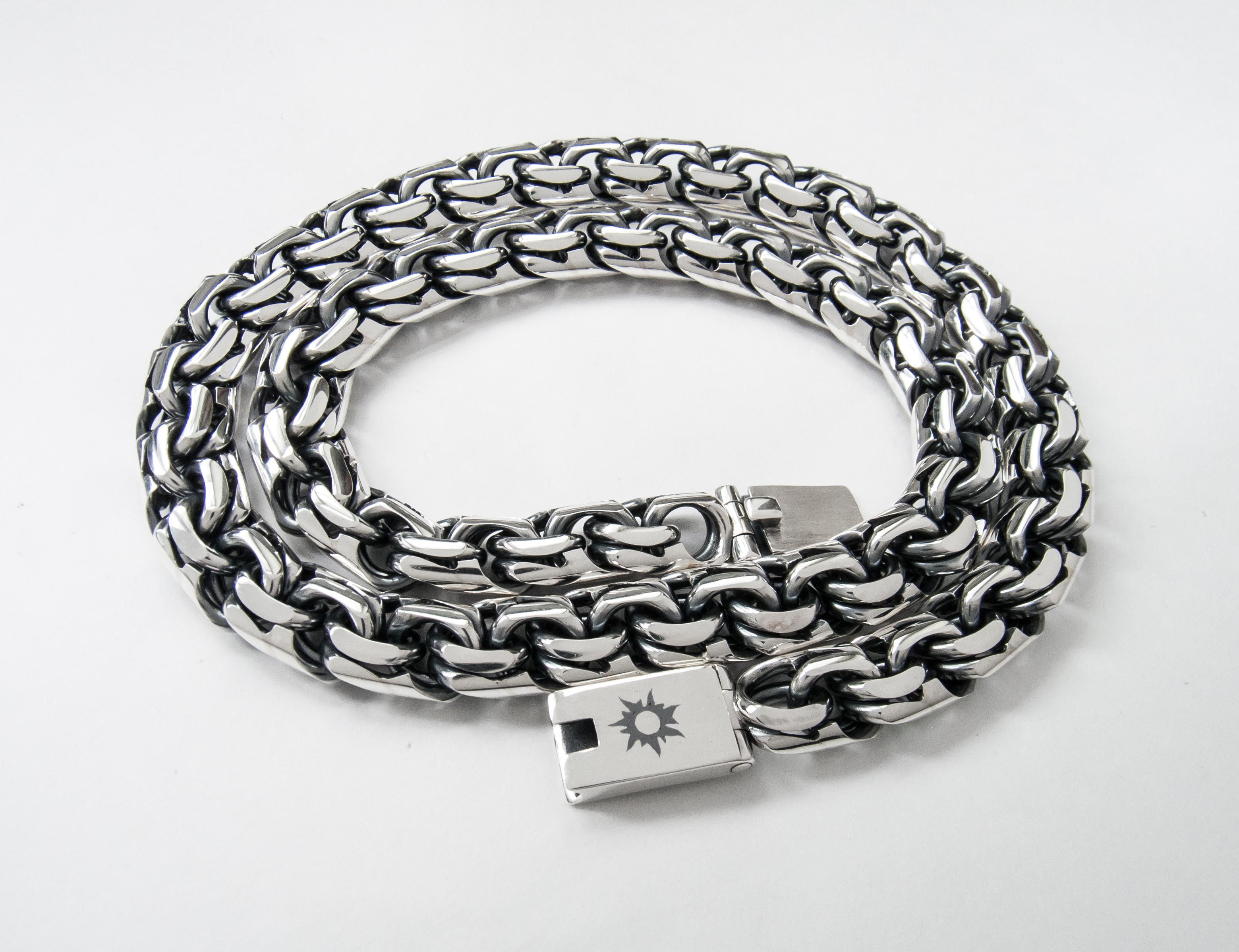 Гравировка на замке серебряной цепи символа солнца